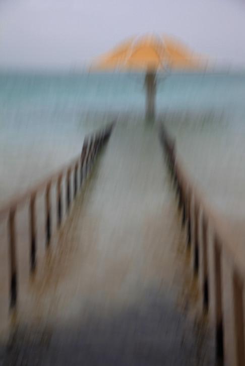 A blurred path into the sea and a yellow umbrella