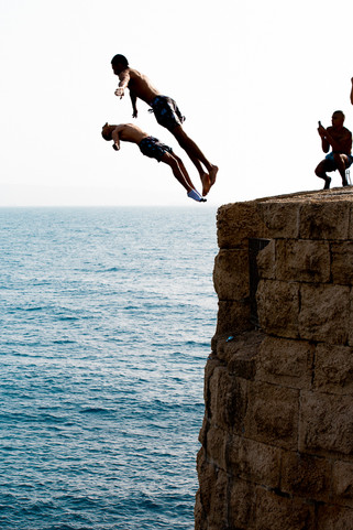 two men jumping off a Cliff