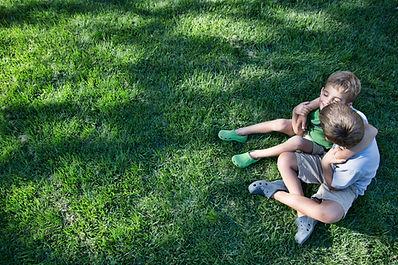 rodzeństwo obejmujące się na trawie