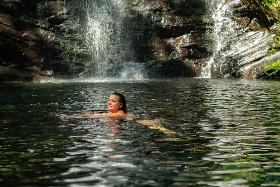 Travel blogger Rosanna Stevens swimming in a waterfall in Belize
