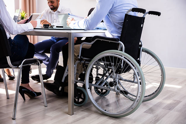 Office colleagues sat around a table with one person using a wheelchair