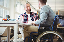 Two men talking in an office environment with one who uses a wheelchair