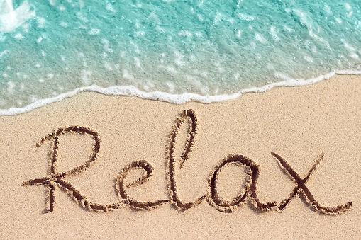 Word Relax handwritten on sandy beach.jp