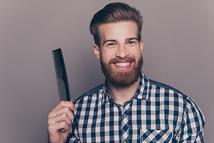 Portrait Of Handsome Cheerful Bearded Young Man Showing His  Black Little Comb.jpg