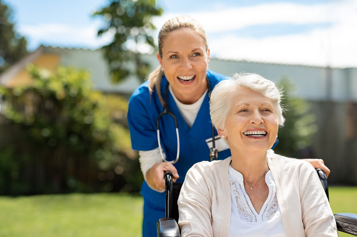 Happy nurse and elderly woman sitting in