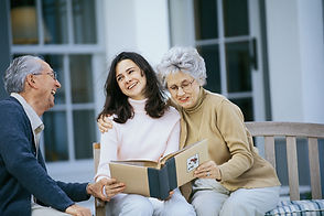 Daughter with long dark hair is seated on an outdoor bench with her mother, who has grey short hair. Her mother has her right arm wrapped around her daughter and they she is looking at a photo album. The father is facing the ladies and smiling, his left hand is wrapped around his daughters right hand. They are all a happy eminiscing family.