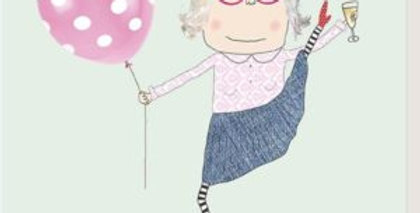 "Older lady dancing with leg in air holding glass of fizz and a balloon with message ""You've still got it"""