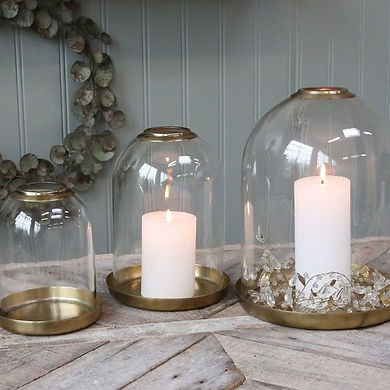 White candles in glass bell jars