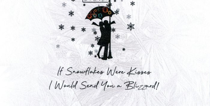 Christmas card featuring silhouetted couple in a snow shower with words If snowflakes were kisses I would send you a blizzard