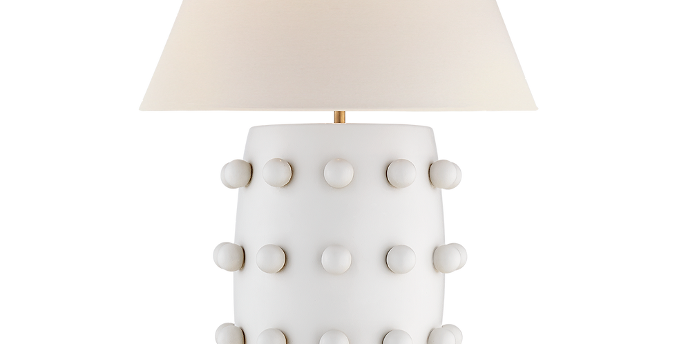 Amatte white table lamp decorated with white bobbles, a large linen shade and antique brass fixings