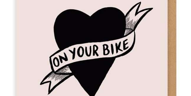 pale pink background with black tattoo style heart and white ribbon with words on your bike