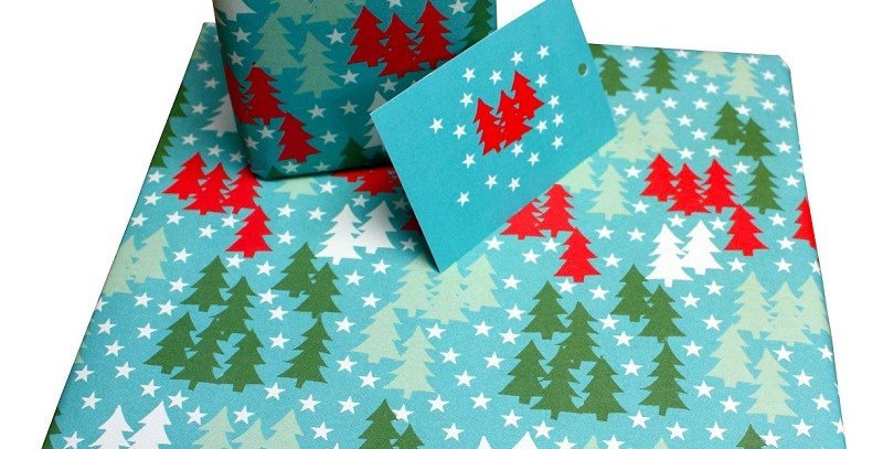 Christmas gift wrap with aqua background and groups of green, white and red christmas trees with white stars. Matching gift t