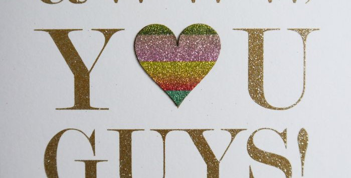 Cream engagement card with gold wording aww you guys you got engaged. the o in you is a multicoloured heart