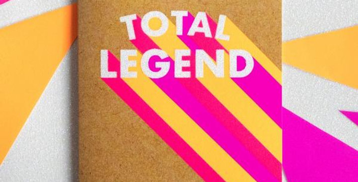 Birthday card which is kraft card with neon pink, purple and yellow beams going to white text saying total legend