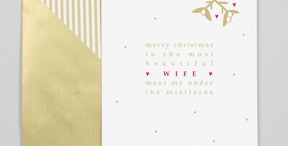 """White card with gold dots and gold and red writing """"Merry Christmas to the most beautiful wife meet me under the mistletoe"""""""