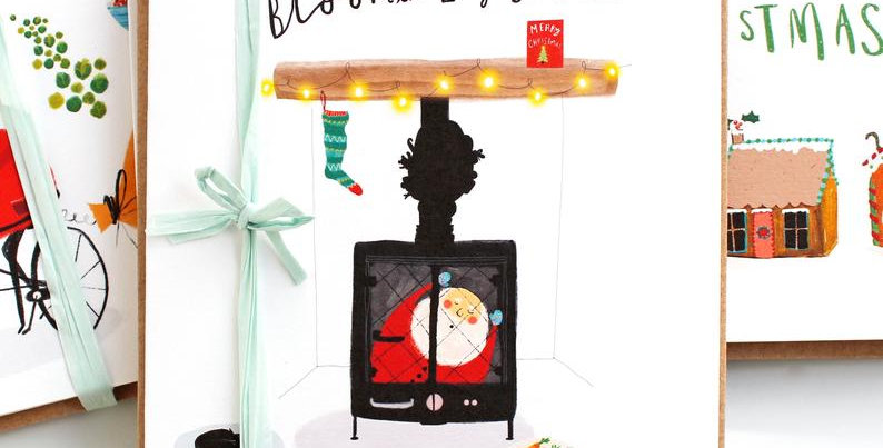 christmas card with santa stuck in a log burner and wording bloomin log burners