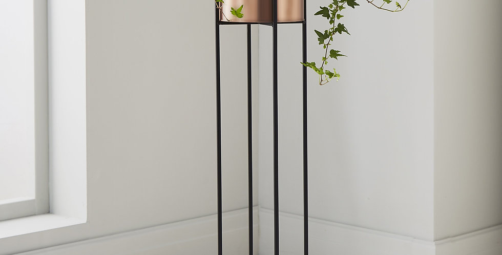 a plant pot that sits on raised black metal legs and has a copper plant pot
