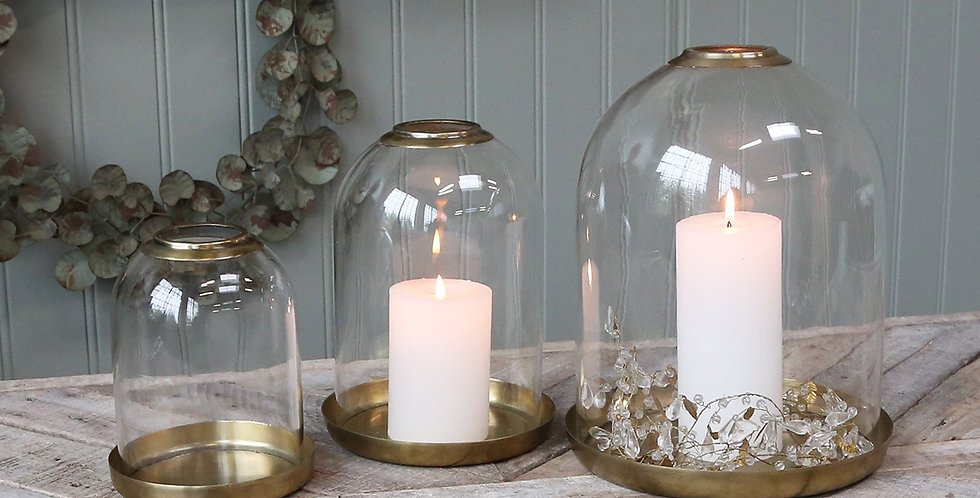 elegant glass bell jar with a brass tray and opening for a pillar candle