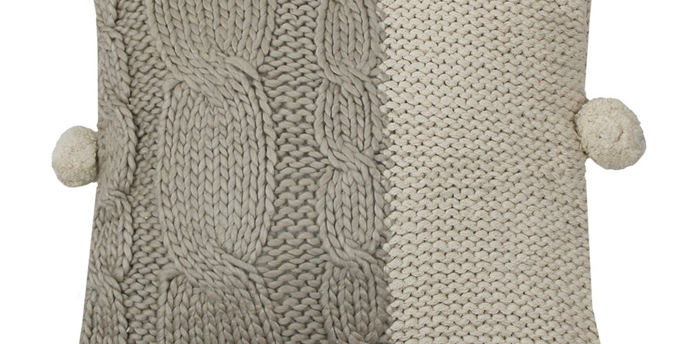 Knitted cushion with 3 pom pom to 2 side edges one half mid grey the other half natural colour
