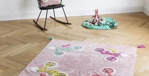 square pale pink rug with bright coloured bicycle design and yellow fringes to each corner, perfect for kids bedrooms