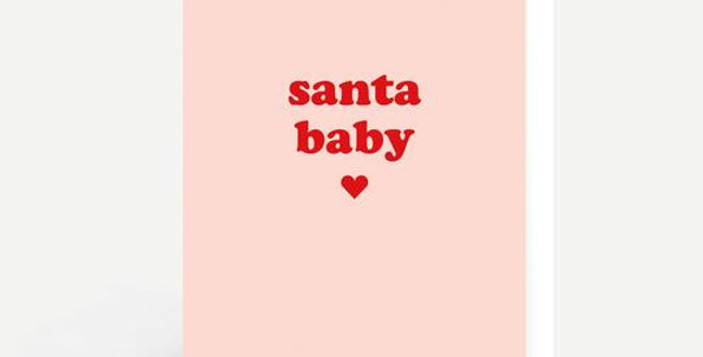 Pale pink background with red heart and wording santa baby