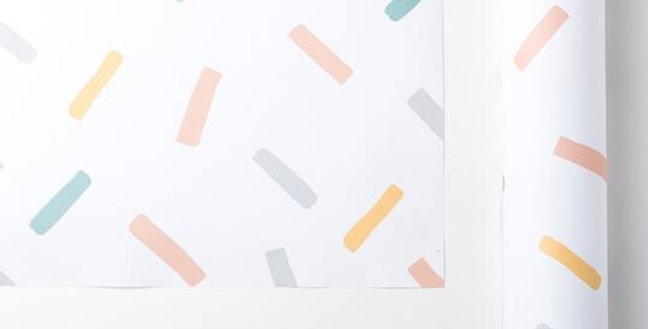 Confetti wrapping paper, white background with yellow, grey, green and pink confetti
