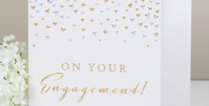 Classy engagement card with gold and silver confetti to top third and gold writing saying On Your Engagement
