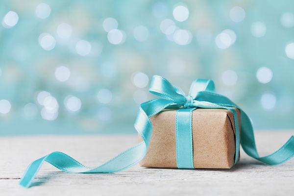 Christmas gift box against turquoise bok
