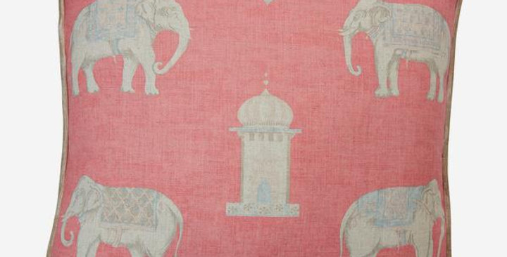 coral pink linen blend cushion showing small painterly natural coloured elephants padding through a dusty landscape