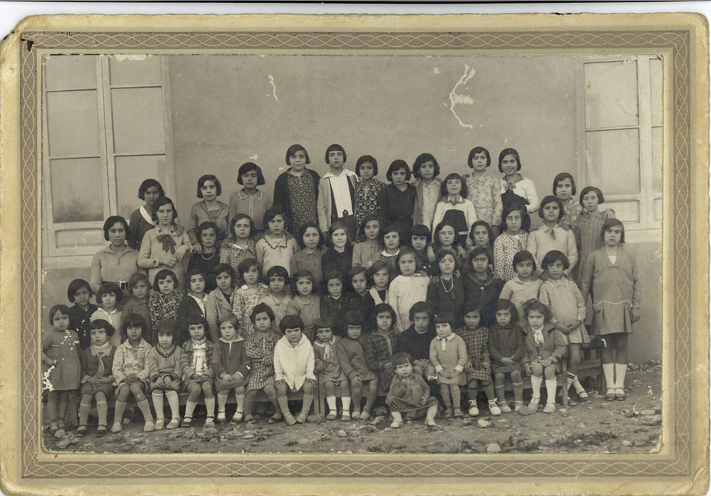CURS 1932-33. Xiquetes. Professora acompanyant, Carmen Jover (filla de la mestra titular, Carmen Jover Cartagena) 1ª Fila dalt (Esquerra a dreta): 1.-Maria ( la Coetera), 2.-Maria Verdú (la Perellona),3.- Carmen Giner, 4.-Maria Martínez (la Borrega). 5.-Juanita Sanjuan, 6.-Otilia Climent, 7.-Carmen Pastor (la Fornera), 8.-Ernestina Esplà. 9.-Maruja (Xalaca), 10.-Carmen (la del Quarter), 11.-Vicentica (Xalaca). 2ª Fila: 1.-Carmen Fernández Jover, 2.- Carmen Molla,3.-Concha Pastor (Conxeta Margarita), 4.-Mercedes Ramos (la Peixera), 5.-Virtudes Pastor (la Fábrica),6.-Maruja (Masa), 7.- Maria Giner (la Roja), 8.-Milagros Brotons (el de Soqui), 9.-Lola (la Xana). 10.-Rafaela Pastor (el Desculat), 11.-Fina (Masa), 12.-Lola Brotons (la Carrilla), 13.- Carmen (la Coix), 14.-Trinita (la filla del metge), 15.-Tonica (la Municipala), 16.-Leonor Blasco (la Casinera), 17.-Maria Sánchez (Barragan). 3ª Fila: 1.-Maria Sánchez, 2.-Loreto (la Xana), 3.-Encarna Brotons (la Carrilla),4.-Nieves Climent, 5.-Isabel Antón (la Mosquita), 6.-Maria (la Pallera), 7.-Carmen Sánchez (Barragan), 8.-Encarna, 9.-Maria Pastor (la Maja), 10.- Mercedes (el Roig), 11.-Vicentica Emma o Conxa Ripoll, 12.-Paquita( EL Roig), 13.-Loreto (Rebolica), 14.- Lola Martínez (la Borrega), 15.-Enriqueta (el Quarter), 16.-Pepica Sánchez (Barragan), 17.-Lola Verdú (la Cotxera). 4ª Fila: 1.-Maria Juan (Maria Roc), 2.-Lola (la Sorda), 3.- Concha Verdú (la Santjoanera), 4.-Erundina Blasco, 5.-Laura (Masa), 6.-Maria Giner (la Torrera), 7.- Ana (Pepino), 8.-Amelia Ramos (la Peixera), 9.- Eloina Aracil, 10.-Eulalia Blasco (la Figuera), 11.-Carmen Pastor (la Maja), 12.- Rosa (San José), 13.-Herminia Verdú (la Perellona), 14.-Mª Loreto (la Padrenuestra), 15.-Trinita (la del Chato), 16.-Remedios Soler (Pelailla), 17.-Delia (Xalaca) (sentada davant).
