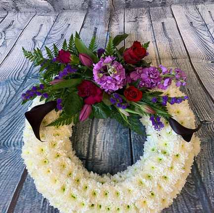 white based funeral wreath tribute with purple posy.jpg