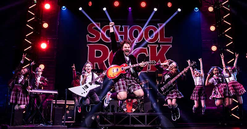 School of Rock cast jumping on stage