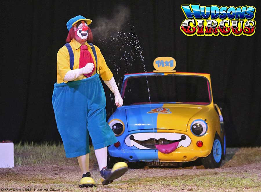 Goldie the Clown being sprayed with water by his car