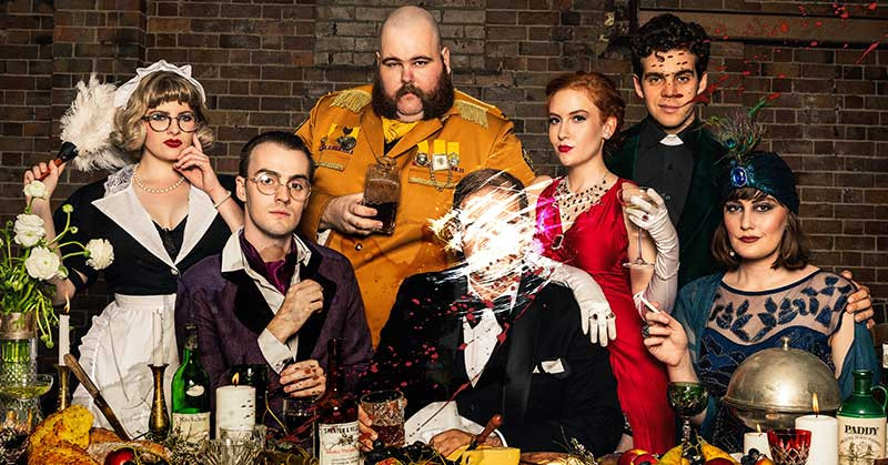 Cluedo! The Interactive Game cast of 2018 sitting around a dining table with the murder victim's face scratched out in the photo
