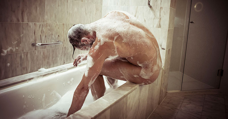 man leaning on edge of bath, covered in suds.