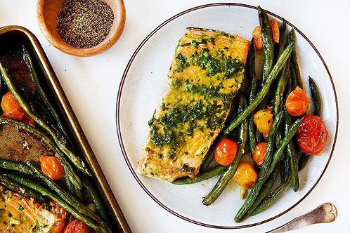 Herb butter salmon with blistered vegetables and a roll