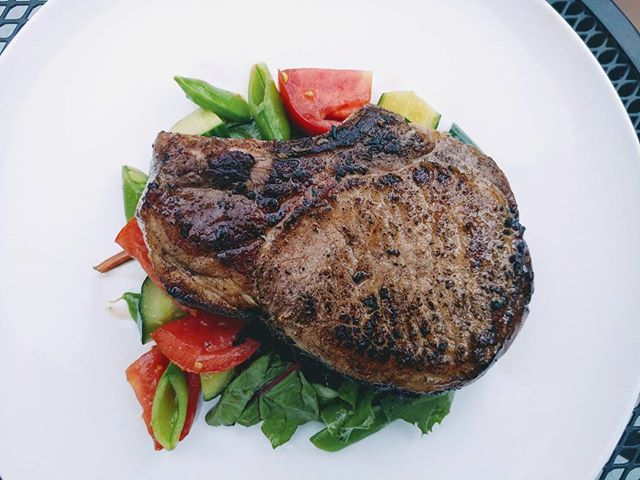 Sous vide koji encrusted pork chop, flashed in butter atop heirloom tomatoes, snap peas, cucumber, a