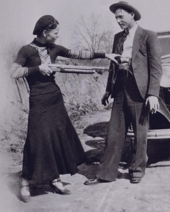 Bonnie 'holds up' Clyde with the shotgun of a murdered police officer