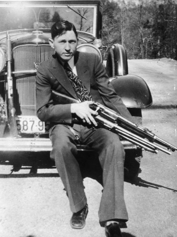 Clyde poses in front of the stolen Ford v8 they used to evade the law