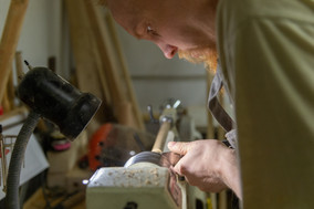 man-working-at-workshop-holding-a-metal-