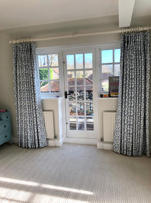 Studio G terrace trail fabric in floor length curtains with a chunky white pole.