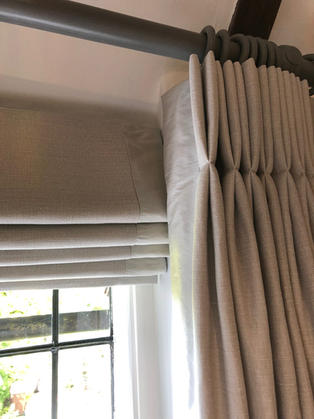 A roman blind and curtains can be used together for a unique window dressing.