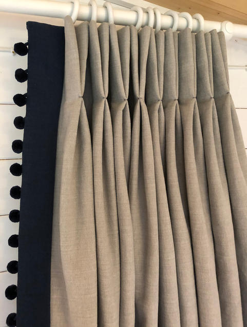 Lovely grey curtains with a contrast leading edge in navy fabirc with navy pom poms for a truly bespoke look.