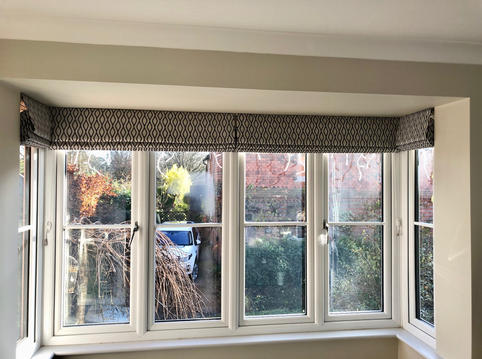 A square bay window with roman blinds made in a Clarke & Clarke fabric.