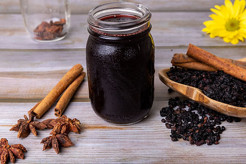 Elderberry Syrup in a glass jar with the elderberries and other ingredients spread around