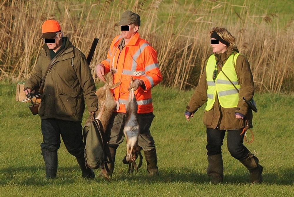 Jäger nach der Treibjagd mit Feldhasen