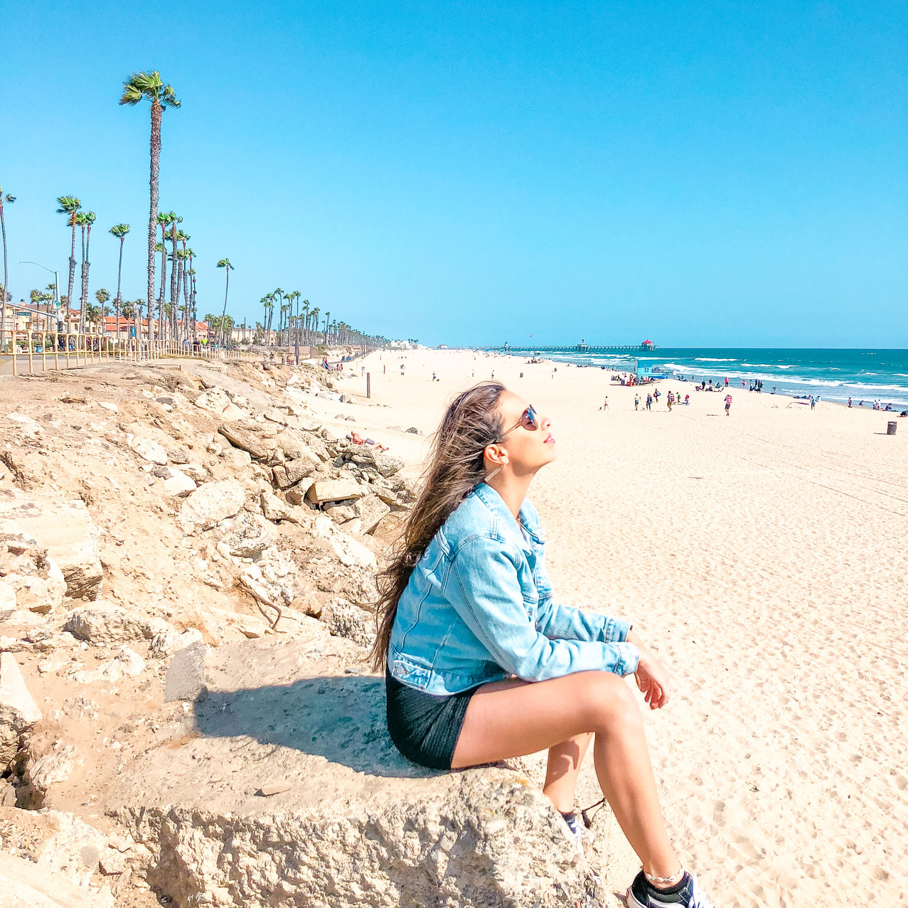 girl sitting on beach cliffs on a clear day