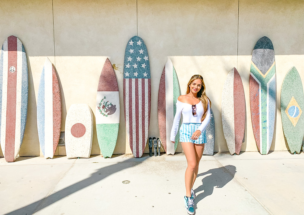 surfboards decorated with countries flags and a girl