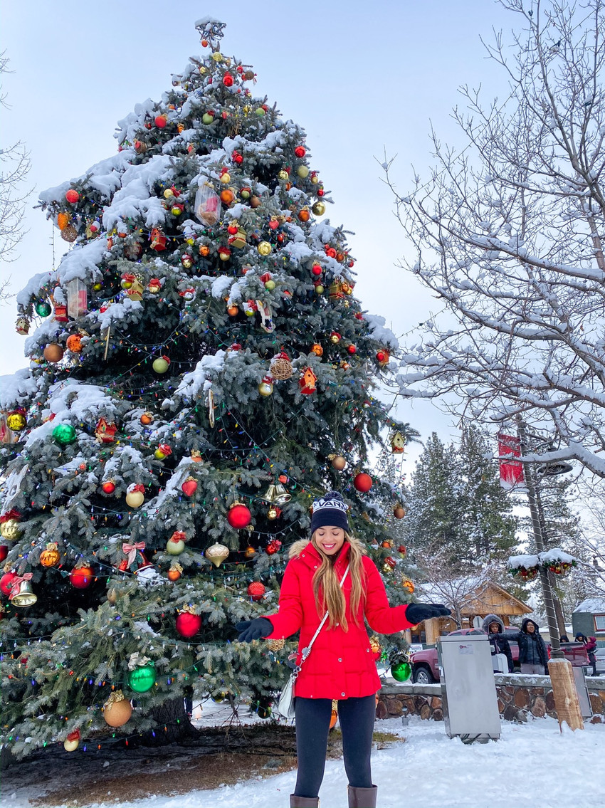 Girl in front of snowy Christmas tree