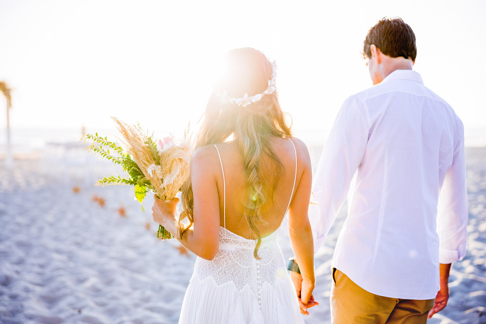 newlywed couple walking on the sand holding hands